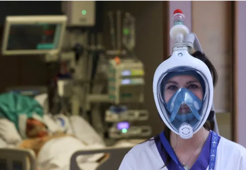 A nurse wears a full-face snorkelling mask that has been adapted by an Italian firm to make a ventilator using parts made on a 3D printer in the UK.